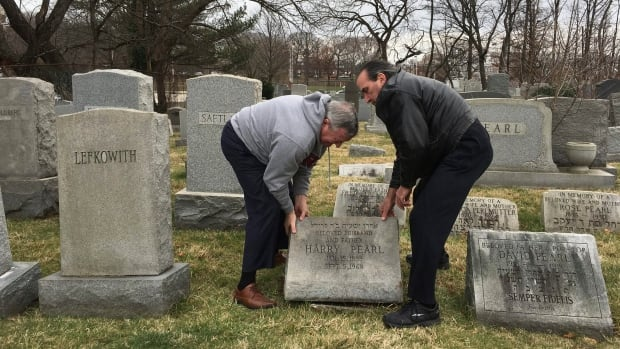 "Philadelphia Mayor Jim Kenney, left, helps David Pearl Jr. lift up the headstone of Pearl's grandfather, at Mount Carmel Cemetery Monday in Philadelphia. Police investigated what they called an ""abominable crime"" after several hundred headstones were damaged during the weekend at the Jewish cemetery dating to the late 1800s."