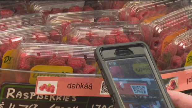 A smartphone reads a code on the label for raspberries. The code redirects the phone to a webpage that hosts a voice recording of the Slavey word.
