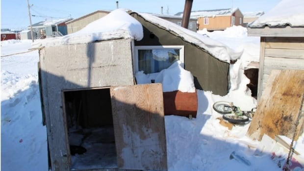 A young family in Igloolik, Nunavut, lived in this poorly constructed wooden shed. New federal funding allocates $240 million to Nunavut, which will be used to build new homes, says housing corporation.
