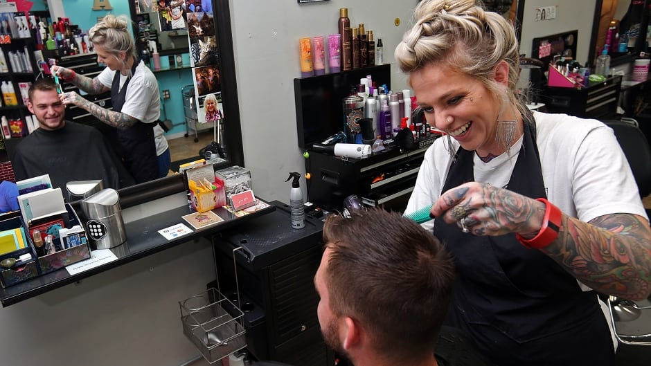 Hair stylist Jamie Feramisco shares a laugh with a client at Pin-Up Hair Studio in Quincy, Illinois. In January 2017, an Illinois law took effect that mandates training for stylists like Feramisco so they can support people affected by domestic violence.