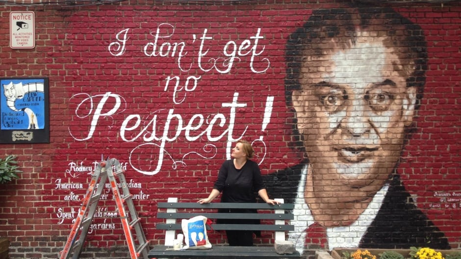 Francesca Tosca Robicci poses with the mural she painted of Rodney Dangerfield in the Queens borough or New York City.