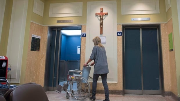 A hospital employee walks to the elevator at the main entrance of the Saint-Sacrement hospital, where a crucifix was re-installed following hundreds of complaints.