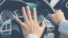 Road rage, driver's hand on steering wheel
