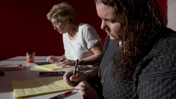 Sarah Bezanson, right, and Martha Cody write letters calling for a judicial council review of Judge Gregory Lenehan during an organized letter-writing event in Halifax on Sunday.