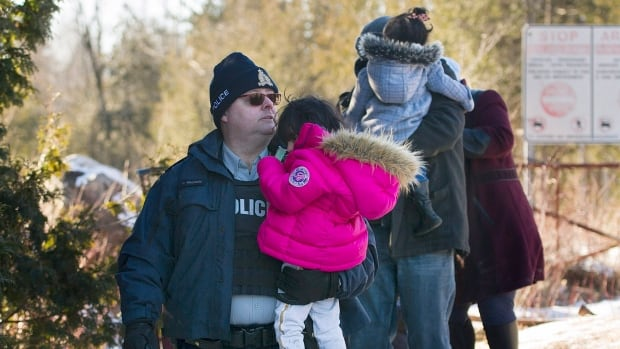An RCMP officer escorts a family as they cross the U.S.-Canada border in Hemmingford, Que., on Sunday.