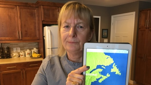 Marie Gilchrist holds up a picture she took of a map at the Vancouver International Airport that is missing P.E.I.