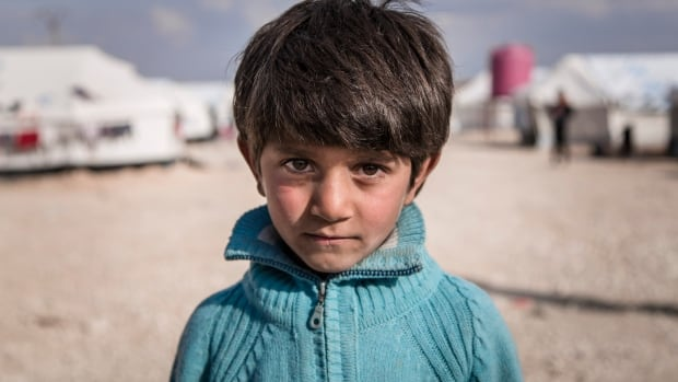 Ibrahim, 7, poses next to his family's tent in Al Hol Camp, Hasakah Governorate, Syria.