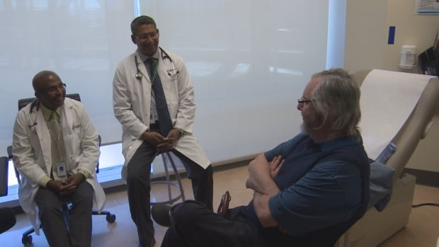 Dr. Gavin Oudit (left) and Dr. Rathnadeep Basu (centre) speak with Dale Roberts, a heart research patient at the University of Alberta.