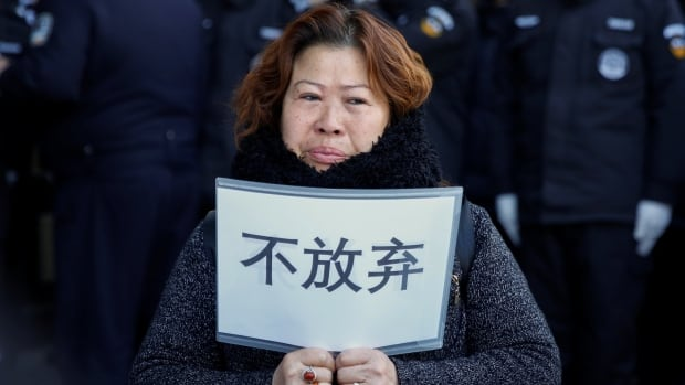 A relative of a passenger aboard Malaysia Airlines flight MH370, which went missing in 2014, holds up a placard outside the foreign ministry in Beijing on Wednesday. The placard reads: 'Don't give up.'