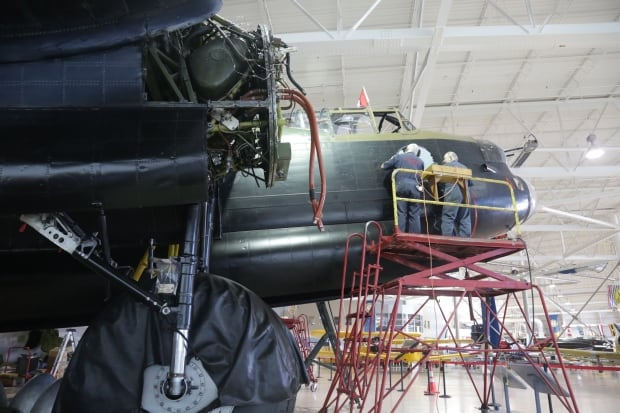 Workers remove an old decal from the Lancaster.