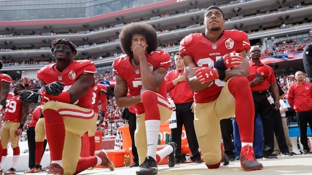 San Francisco 49ers linebacker Eli Harold, quarterback Colin Kaepernick, centre, and safety Eric Reid kneel during the national anthem before a game against the Dallas Cowboys in October. Kaepernick is still looking for employment next season, but isn't expected to continue his anthem protests.