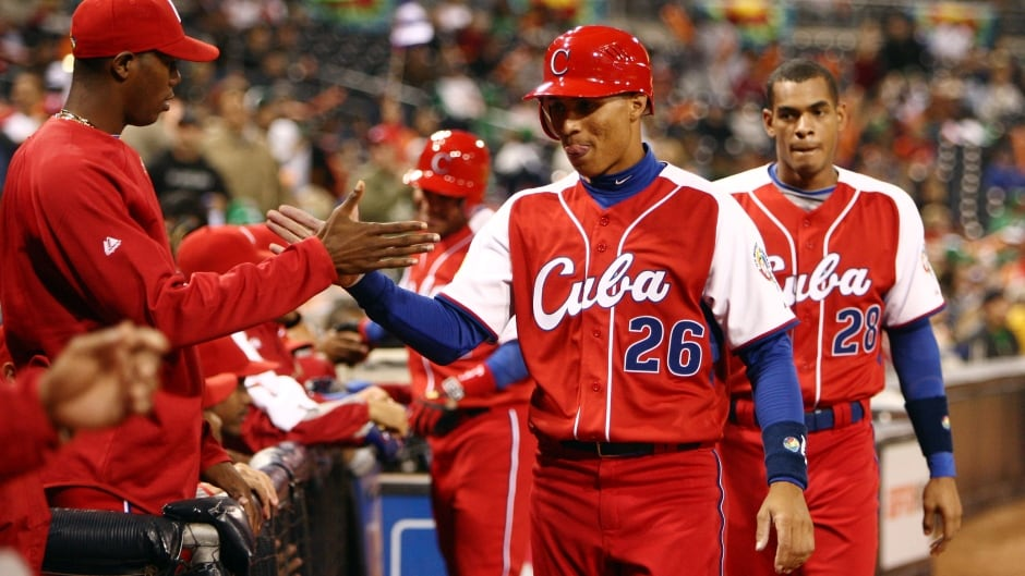 Leonys Martin #26 and teammate Hector Olivera #28 are congratulated by teammates during the 2009 World Baseball Classic in San Diego, California. Martin and Olivera have since defected to the U.S.