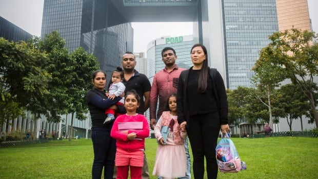 Some of the individuals who provided accommodation to Edward Snowden while he was in Hong Kong pose with their children in front of the government buildings of Hong Kong on Feb. 23. The families say they hid Snowden in their apartments for weeks in 2013 before he went to Russia.