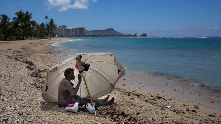 In this 2015 photo, a homeless man drinks water while sitting on the beach near Waikiki in Honolulu, Hawaii.