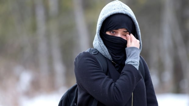 A woman claiming to be from Yemen wipes tears from her eyes as she is told not to enter the U.S.-Canada border into Hemmingford, Que., on Feb. 22. The woman crossed the border despite being told not to and was arrested.
