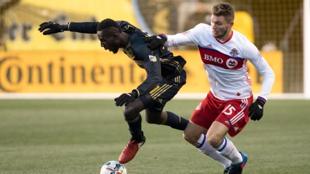 Philadelphia Union's Derrick Jones, left, gets pushed by Toronto FC's Eriq Zavaleta, right, as they go for the ball during the second half.