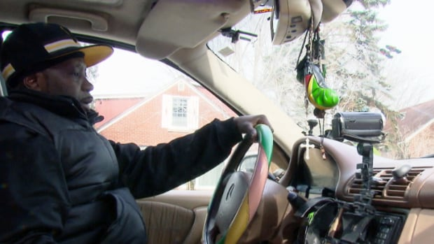 Kenrick McRae in his Mercedes with a camera on the dashboard - he uses it to record police who stop him every month or two, he says.