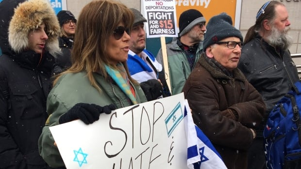 People gathered outside Miles Nadal Jewish Community Centre with signs and Israeli flags Monday.