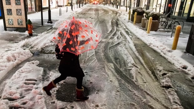 A woman crosses a street during the storm in Philadelphia, where schools were closed Tuesday.