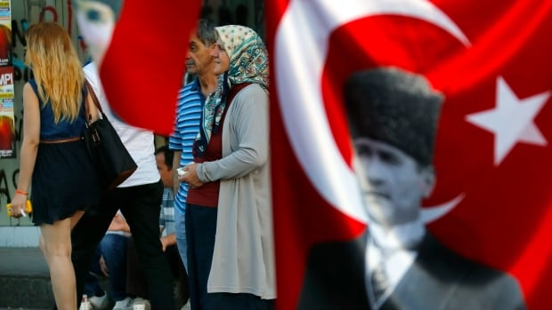 Secular and religious Turkey in a nutshell. A scene in Istanbul's Taksim Square is framed by a flag with the image of Mustafa Kemal Ataturk, the founder of modern Turkey.