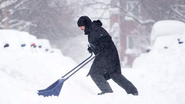 A man shovels snow from around his car following a winter storm.
