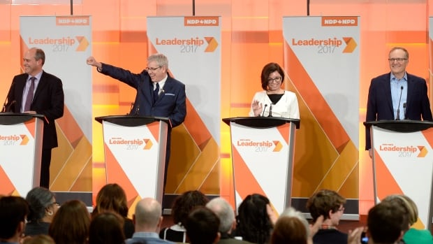 Guy Caron, left, Charlie Angus, Niki Ashton and Peter Julian react to the audience as they arrive on stage for the first debate of the federal NDP leadership race, in Ottawa on Sunday, March 12, 2017.