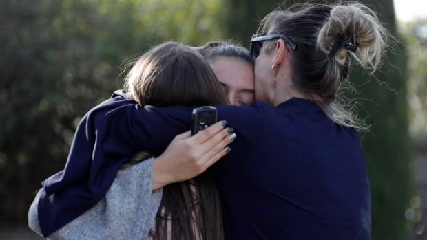 People embrace near the high school in Grasse, France, after the shooting took place.