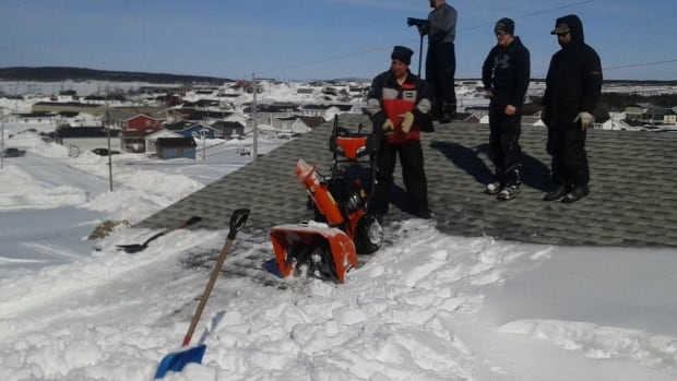 Rick Cooper and some neighbours taking a break from snowblowing the roof of his house.