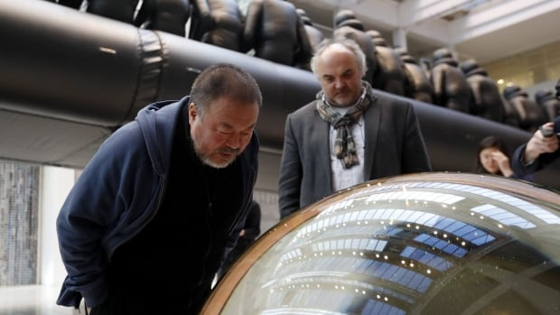 Ai Weiwei, left, looks into a glass ball that is part of his installation at the National Gallery in Prague on Thursday.