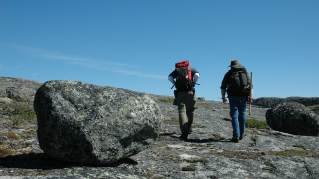 Researchers Jonathan O'Neil and Don Francis returning to camp with backpacks full of rock samples.