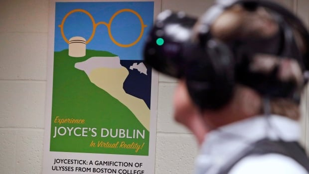 Boston College English professor Joseph Nugent wears virtual reality goggles to test out Joycestick, a virtual reality game his students are creating based on James Joyce's ponderous tome Ulysses.