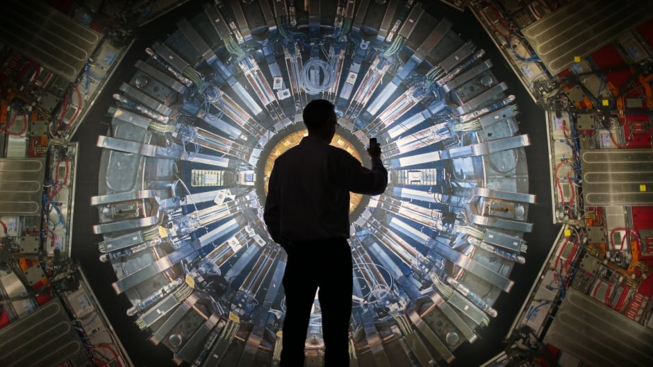 A visitor takes a phone photograph of a large back lit image of the Large Hadron Collider (LHC) at the  Science Museum's 'Collider' exhibition in London, England in 2013. It touches on the discovery of the Higgs boson, or God particle, the realisation of scientist Peter Higgs' theory.