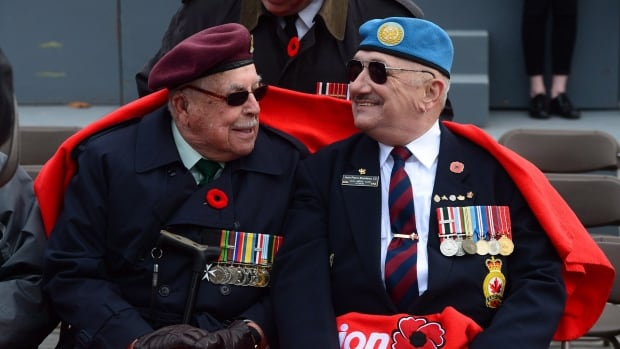 Veterans Joe Quinn, left, and Jean-Pierre Riendeau take part in a Remembrance Day ceremony at the National War Memorial in 2016. Next week's federal budget will restate the Liberals' campaign promise of returning younger injured veterans to a system of lifetime pensions, sources have told CBC News.