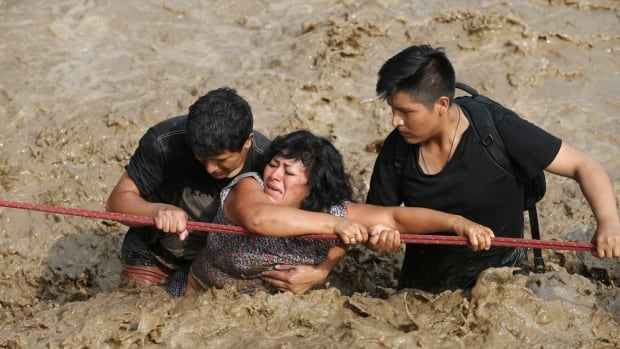 A woman is assisted while crossing a flooded street on Friday after the Huaycoloro river overflooded its banks in Huachipa.