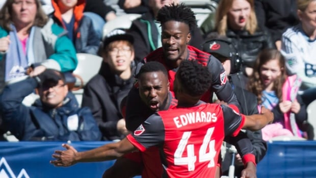 Toronto FC's Tosaint Ricketts, back, Jozy Altidore and Raheem Edwards (44) celebrate Altidore's goal during second half MLS soccer action against the Vancouver Whitecaps.