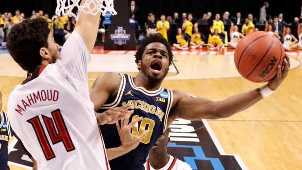 Michigan's Derrick Walton Jr. (10) shoots as Louisville's Anas Mahmoud (14) defends during a second-round game in Indianapolis on Sunday.