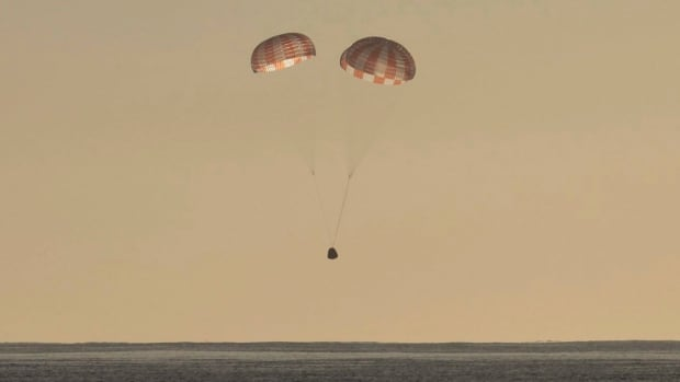 In this photo provided by SpaceX, the Dragon cargo ship parachutes into the Pacific off the Southern California coast on Sunday.
