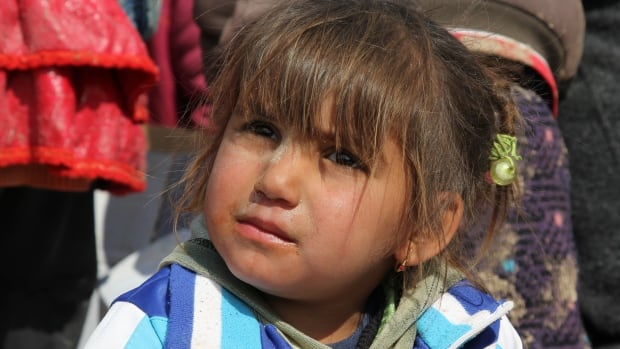 A young Iraqi girl waits with her family at an assembly point for displaced residents of Mosul.