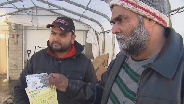 Palwinder Singh Johal (right), shows the receipt for his truck being towed on Tuesday night.
