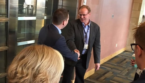 Economic Development Minister Deron Bilous shakes hands with former MP Rob Merrifield