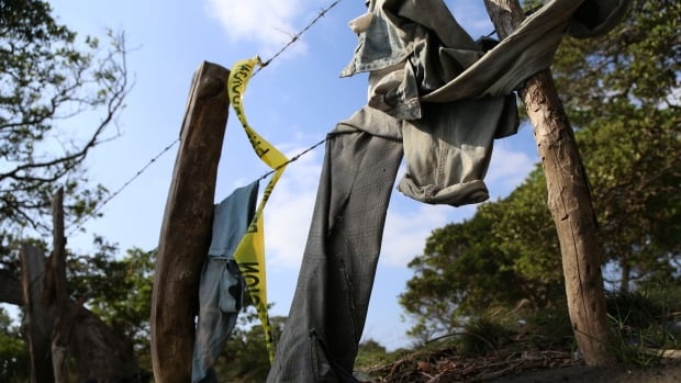 Clothing is seen on March 19 around a mass grave where 12 bodies were exhumed Friday by the authorities in El Arbolillo village in Alvarado, Veracruz state.