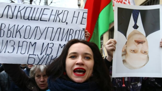 People shout slogans at a protest against taxes and the proposed fine on 'parasites' who have not officially worked half the year, in Minsk, the capital of Belarus, on March 15. The sign reads, 'Lukashenko, stop picking the raisins out of the bread.'