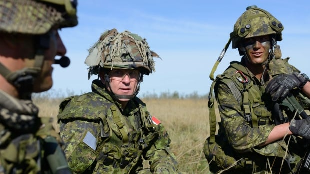 Brig.-Gen. Simon Hetherington, centre, commander 3rd Canadian Division, talks with members of the Loyal Edmonton Regiment during a training exercise in Canada last summer. Hetherington was responsible for training the Canadian elements of the NATO battle group headed to Latvia this summer.