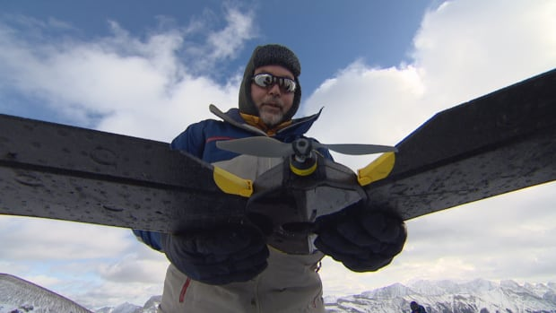 Hydrologist John Pomeroy prepares to launch a drone that will take hundreds of pictures of Fortress Mountain in Kananaskis, Alta.  The pictures are used to create a 3D model that allows the scientists to study the snowpack.