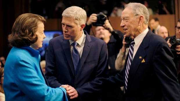 Gorsuch is greeted by ranking member Democratic Senator Dianne Feinstein and Senate judiciary committee chairman Republican Chuck Grassley before the confirmation hearing.