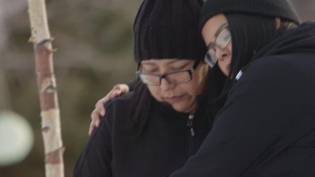 Anita Ross and her daughter Lori embrace at the grave of Ross' daughter Delaine Copenace, who was found dead on March 22, 2016.
