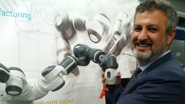Farzad Rayeghani holds one of two robotic arms at Sheridan's engineering lab, worth $100,000 each, donated by ABB-Canada, one of the world's largest engineering firms in robotics and automation technology.