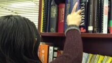 Woman puts book on a shelf