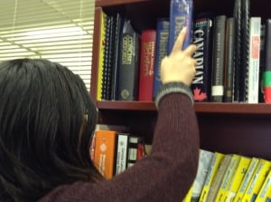 Woman puts book on a shelf