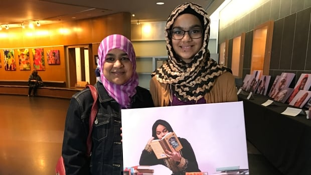 Abiha Syed, organizer of the (UN)Covered Project: Why We Choose to Cover Our Heads, with her daughter Madiha. They're holding a photo taken by photographer Simrin Dhillon.